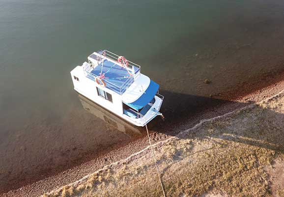 a 21' enclose day boat for hire floating in the coastal saltwater lake for hire from top of the lake boat